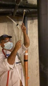 unique providers technician using semi-robotic brush to clean inner walls of duct system